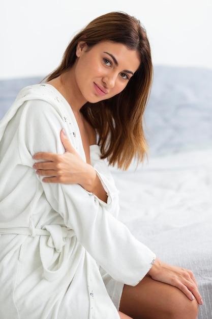 Vista laterale della donna seducente che posa in accappatoio Foto Gratuite