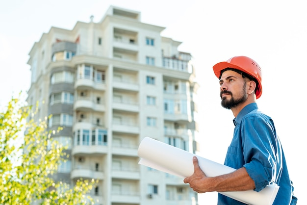 Side view of architect with schematics Free Photo