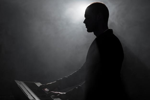 Вид сбоку художника, играющего на пианино с эффектами дыма и теней Бесплатные Фотографии