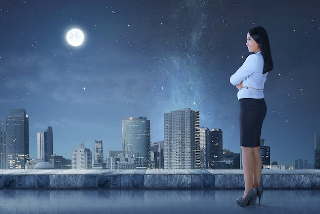 Side view of asian business woman standing on terrace looking cityscape Premium Photo