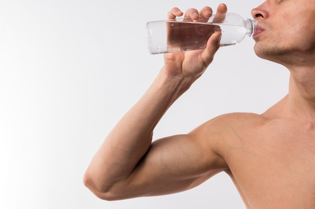 Side view of athletic man drinking water from bottle with copy space Free Photo