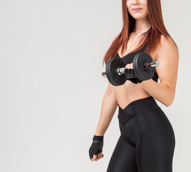 Side view of athletic woman in gym attire exercising with weight Free Photo