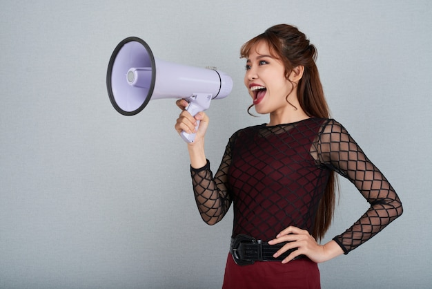 Side view of attractive woman shouting into megaphone with her arm on waist Free Photo