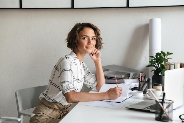 Vista laterale della donna fantastica che si siede dalla tabella Foto Gratuite