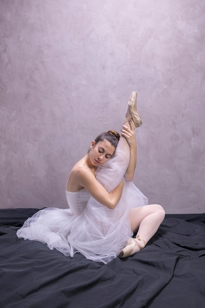Side view ballerina holding her leg up Free Photo