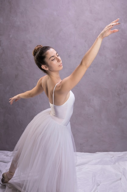 Side view ballerina posture with stucco background Free Photo