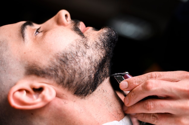 Side view barber shaving client's beard close-up Free Photo
