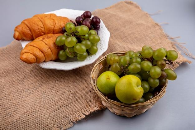 Vista laterale del cesto e piatto di uva con pluots e croissant su tela di sacco su sfondo grigio Foto Gratuite