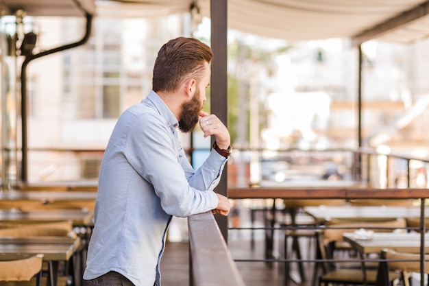 Side view of a bearded man standing in restaurant Free Photo