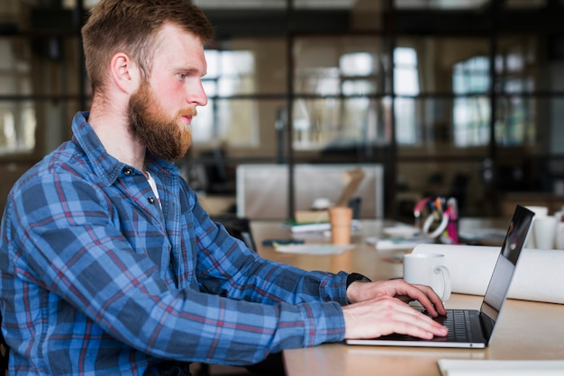 Side view of bearded man wearing blue checkered shirt using laptop Free Photo