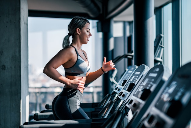 Side view of beautiful muscular woman running on treadmill. Premium Photo