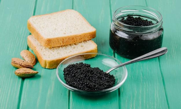 Caviale nero di vista laterale con pane bianco e mandorla del cucchiaio su superficie di legno del turchese Foto Gratuite