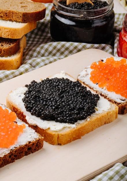 Vista laterale caviale nero e rosso toast segale e pane bianco con ricotta caviale nero e caviale rosso sul tavolo Foto Gratuite