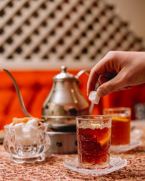 Вид сбоку черный чай с ломтиком лимона и чайником на столе Бесплатные Фотографии