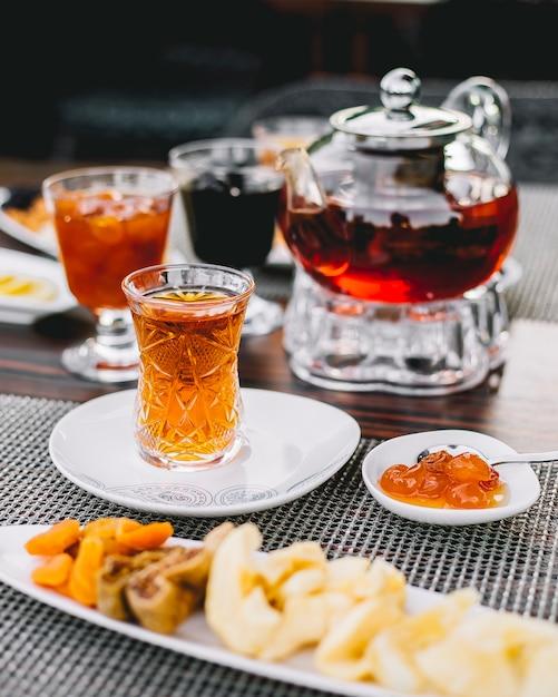 Вид сбоку черный чай с конфетами из белого вишневого варенья и чайника на столе Бесплатные Фотографии