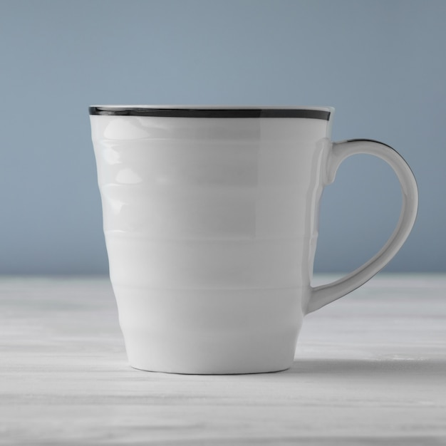 Side view of blank white cup on white table and blue background Premium Photo