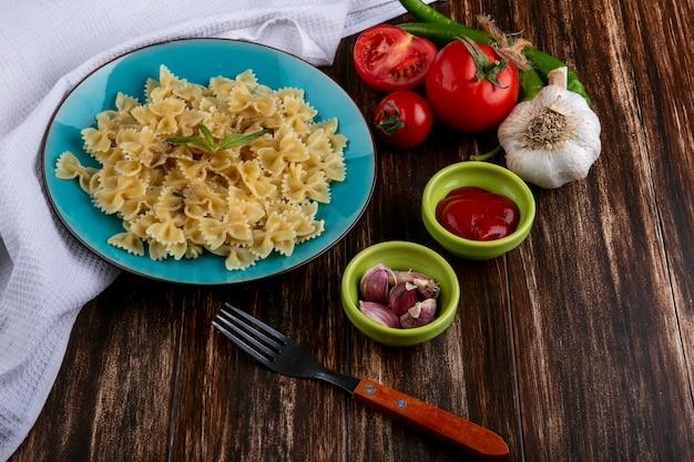 Vista laterale della pasta bollita su un piatto blu con una forchetta pomodori ketchup e peperoncino su una superficie di legno Foto Gratuite