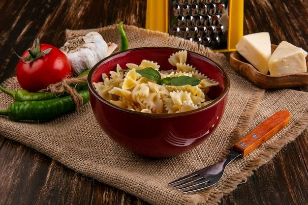 Vista laterale della pasta bollita in una ciotola con una forchetta pomodori peperoncino aglio e formaggio su un tovagliolo beige Foto Gratuite