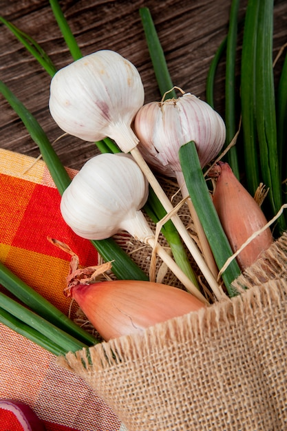 Side view of bouquet of vegetables as garlic shallot and green onion on cloth on wooden background Free Photo