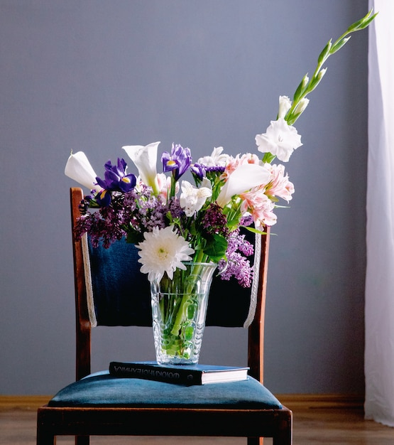 Vista laterale di un mazzo di calle di colore bianco con iris viola scuro lilla e fiori bianchi gladiolo in un vaso di vetro in piedi su un libro su una sedia a sfondo grigio muro Foto Gratuite