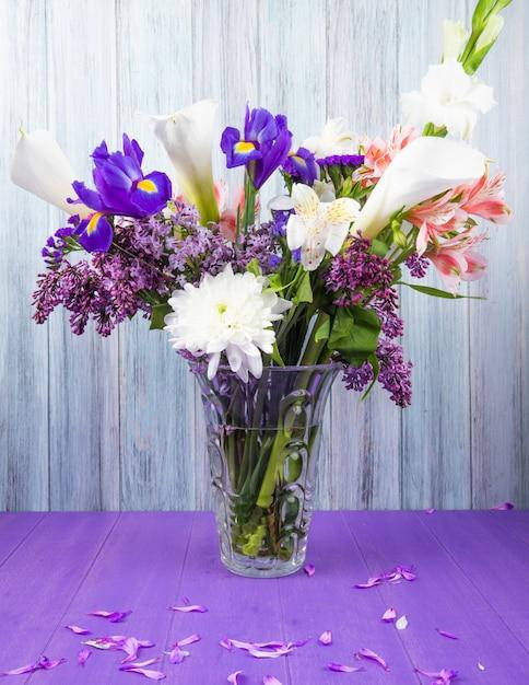 Vista laterale di un bouquet di calle di colore bianco con iris viola scuro lilla bianco gladiolo e fiori rosa alstroemeria in un vaso di vetro sulla superficie viola su sfondo grigio in legno Foto Gratuite
