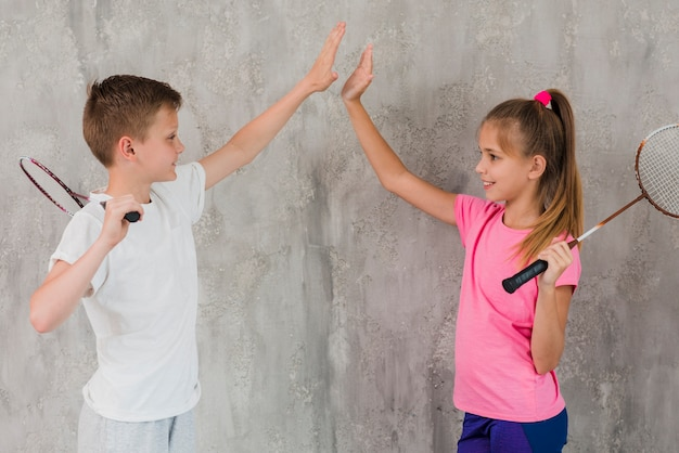 Side view of a boy and girl holding racket in hand giving high five standing against wall Free Photo