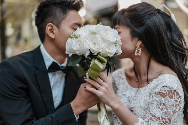 Vista laterale della sposa e dello sposo che nascondono i volti dietro il mazzo di fiori Foto Gratuite