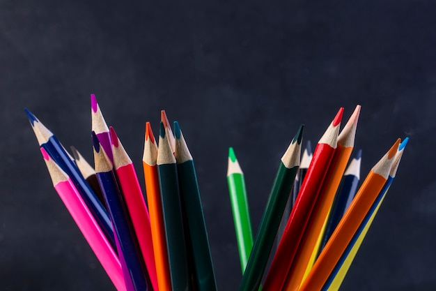 Side view of a bunch of colored pencils on dark Free Photo