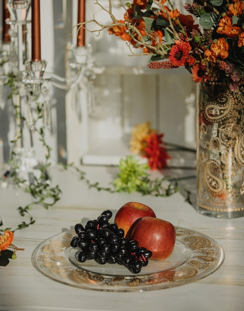 Side view of bunch of grapes and apples on a plate with buta pattern on a wooden table Free Photo