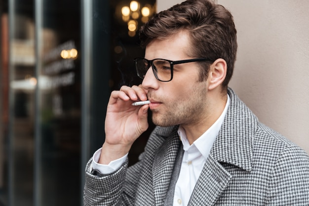 Side view of businessman in eyeglasses and coat Free Photo