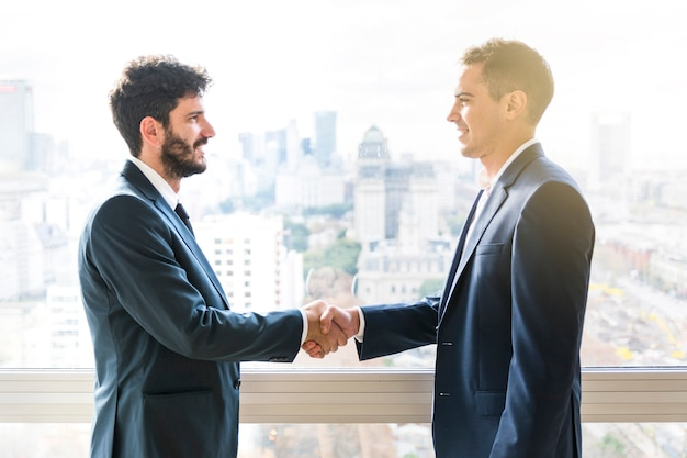 Side view of businessman shaking each other hands Premium Photo