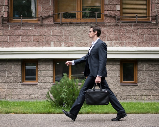 Side view of businessman walking by a building Free Photo