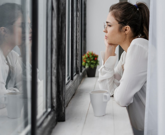 Side view businesswoman looking outside Free Photo
