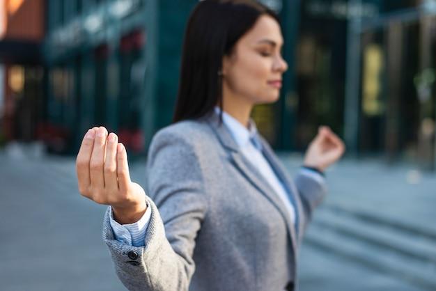Vista laterale della donna di affari nella posa di zen Foto Gratuite
