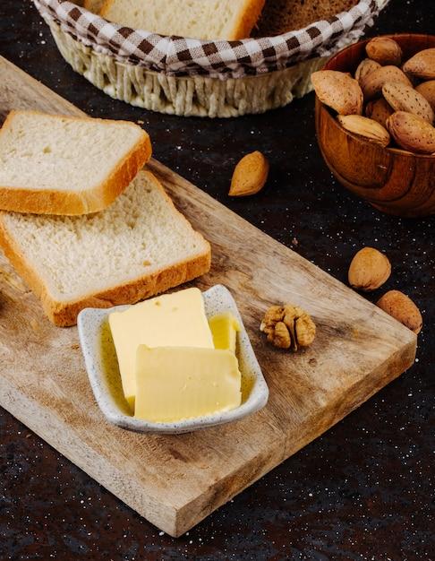 Вид сбоку сливочное масло с белым хлебом миндаля и грецкого ореха на доске Бесплатные Фотографии