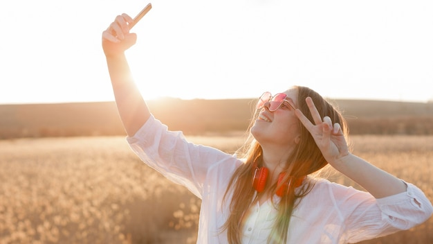 Side view of carefree woman with sunglasses taking a selfie in nature Free Photo