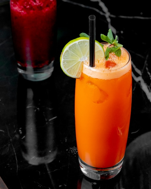 Side view carrot juice with a slice of lime Free Photo