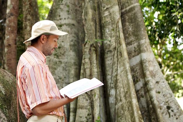 Vista laterale del botanico maschio caucasico in cappello panama e camicia a righe che esplora le specie al lavoro sul campo nella foresta tropicale, in piedi di fronte a una grande pianta, leggendo le informazioni dell'albero emergente nel manuale Foto Gratuite
