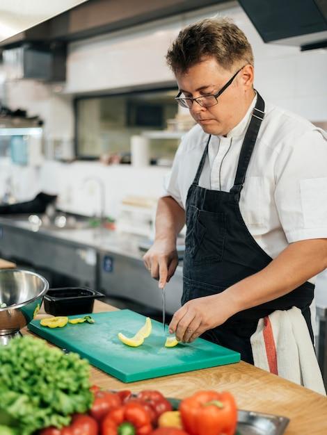 Vista laterale dello chef tagliare le verdure Foto Gratuite