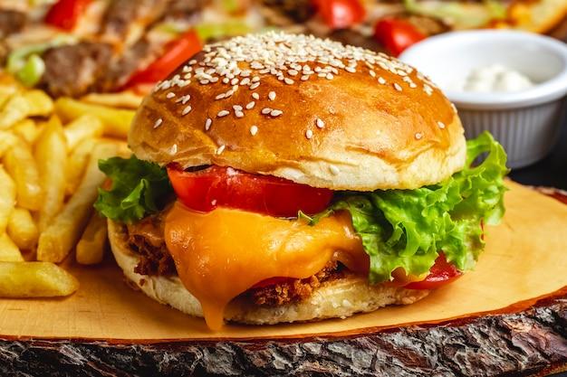 Filetto di pollo cotto a fuoco profondo di hamburger di pollo vista laterale con formaggio pomodoro e lattuga tra panini hamburger Foto Gratuite
