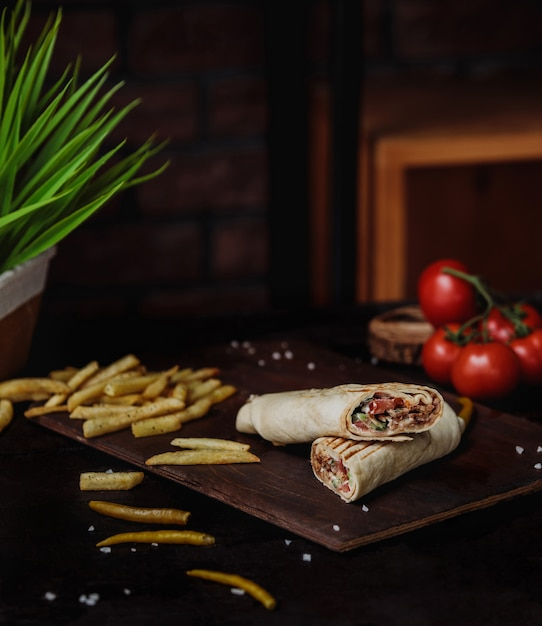 Side view of chicken doner wrapped in lavash and french fries on a wooden cutting board Free Photo
