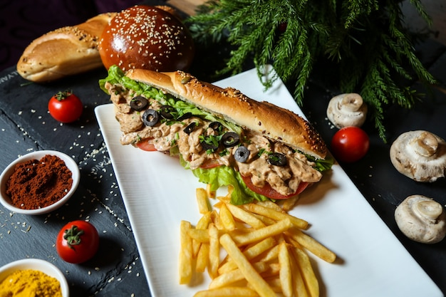 Side view chicken sandwich in bread with fries tomatoes and mushrooms with spices Free Photo