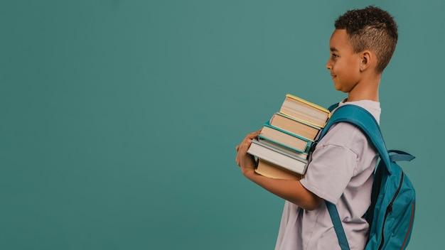 Bambino di vista laterale che tiene una pila di libri copia spazio Foto Gratuite