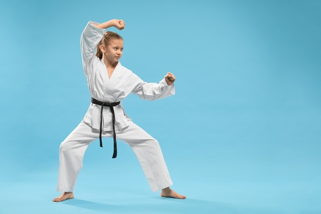 Side view of child standing in karate stance in studio Free Photo