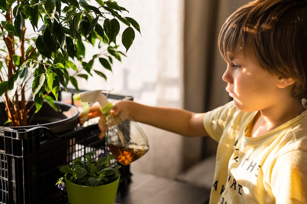 Side view of child watering plants Free Photo