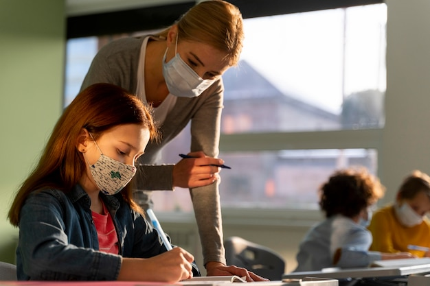 Side view of children learning in school with teacher during the pandemic Free Photo