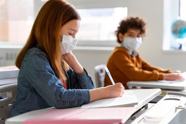 Vista laterale dei bambini con maschere mediche in classe studiando Foto Gratuite
