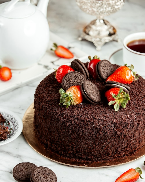 Side view of chocolate cake decorated with strawberries and cookies on the table Free Photo
