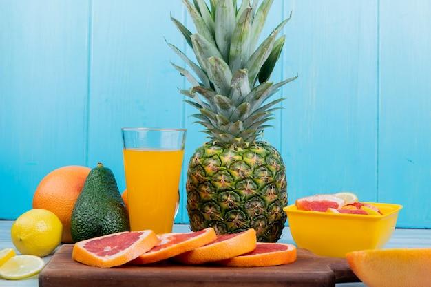 Vista laterale di agrumi come limone avocado ananas con succo d'arancia e fette di pompelmo sul tagliere su superficie di legno e sfondo blu Foto Gratuite