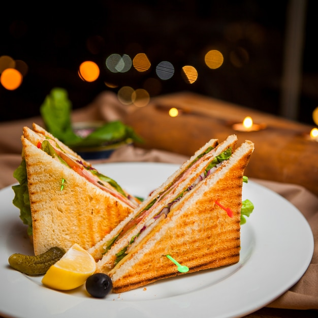Side view club sandwich with salted cucumbers and lemon and olives in round white plate Free Photo